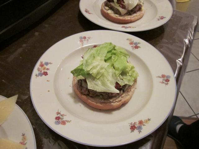 Burger en cours de montage, salade en place
